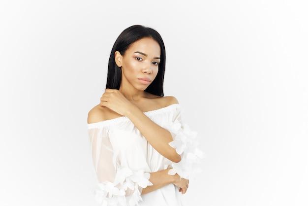 Mulher atraente com aparência africana segurando um modelo de charme de cosméticos para rosto