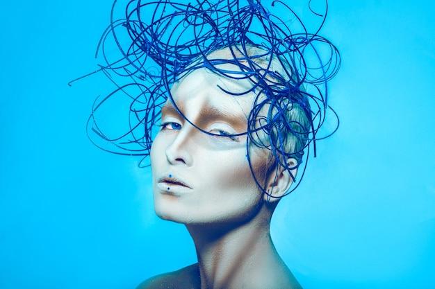 Mulher atraente com arte corporal criativa e penteado na superfície azul