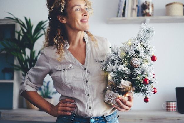 Mulher atraente com árvore de natal decorando a casa para o feriado