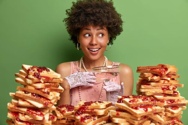 Mulher atraente com cabelo afro cercada por sanduíches de gelatina de manteiga de amendoim