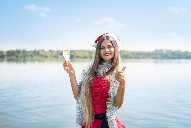 Mulher atraente com cabelo comprido e champanhe na praia