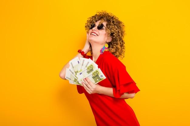 Mulher atraente, com cabelo curto e encaracolado com dinheiro
