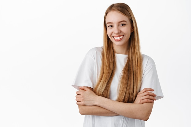 Mulher atraente com cabelo loiro comprido e liso, braços cruzados no peito, parecendo confiante e determinada, sorrindo feliz, em pé com uma camiseta contra a parede branca