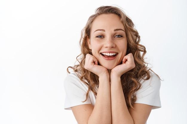 Mulher atraente com cabelo loiro encaracolado, apoiando a cabeça nas mãos e sorrindo, mostrando uma bela pele facial natural sem maquiagem, em pé sobre uma parede branca