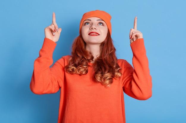 Mulher atraente com cabelo ruivo ondulado apontando para cima
