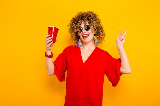 Mulher atraente, com cabelos cacheados curtos e bebida