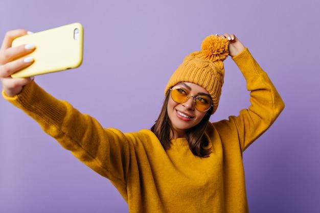 Mulher atraente com características suaves faz selfie em seu smartphone amarelo. retrato de estudante eslavo de bom humor