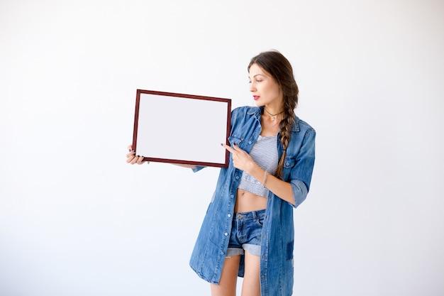 Mulher atraente com cartaz ou cartaz branco em branco vazio