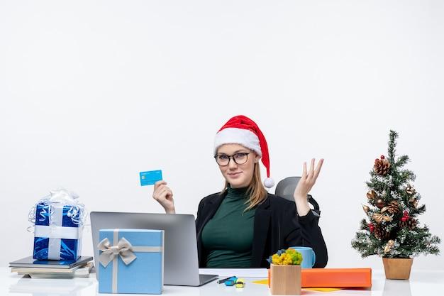 Mulher atraente com chapéu de papai noel e óculos, sentada à mesa e segurando um cartão de banco, perguntando algo no escritório