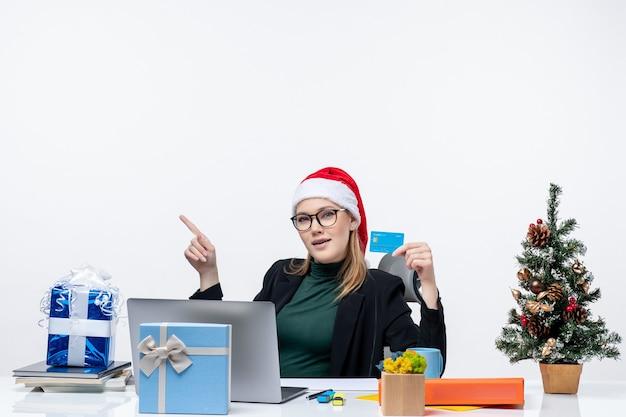 Mulher atraente com chapéu de papai noel e usando óculos, sentada em uma mesa de presente de natal e segurando um cartão do banco na imagem de estoque do escritório