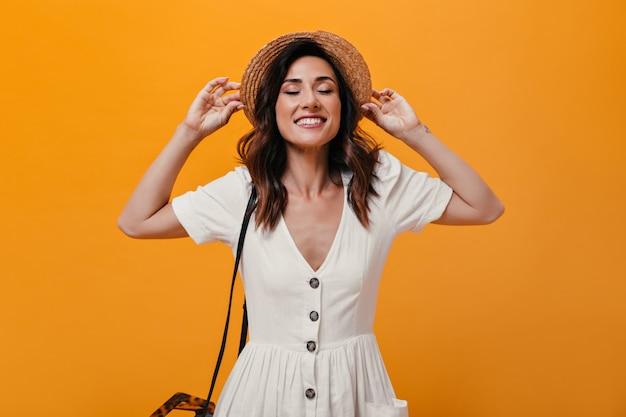 Mulher atraente com chapéu estiloso, sorrindo sinceramente no fundo isolado