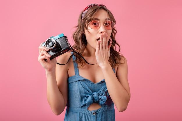 Mulher atraente com expressão emocional surpresa engraçada com câmera vintage em vestido jeans e óculos escuros em fundo rosa