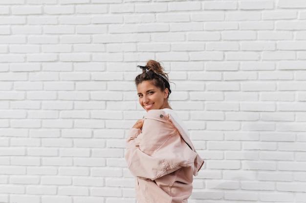 Mulher atraente com faixa de cabelo preta em jaqueta jeans rosa posando contra uma parede de tijolo branco