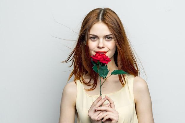 Mulher atraente com flor de rosa e sorriso estilo de vida