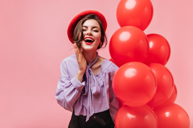Mulher atraente com lábios vermelhos na blusa de seda e boina elegante, ri e posa com balões no fundo rosa.