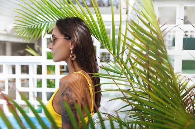 Mulher atraente com lindo bronzeado pose perto da piscina no popular.