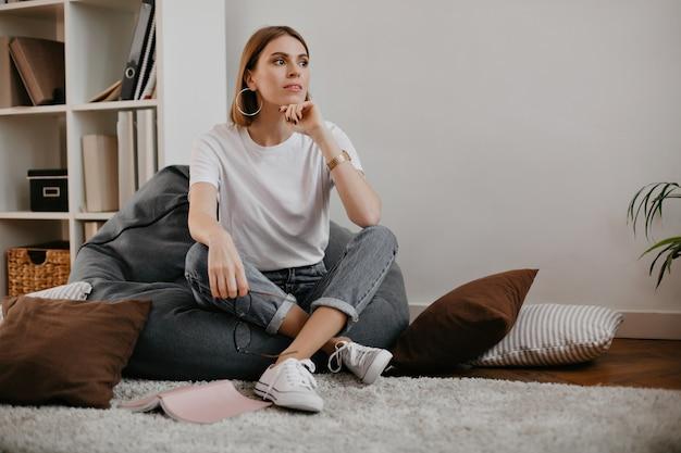 Mulher atraente com lindos brincos maciços e camiseta branca com sorriso, posando enquanto está sentado na poltrona.