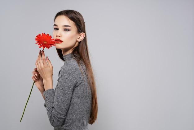 Mulher atraente com luxo de maquiagem glamour de flor vermelha