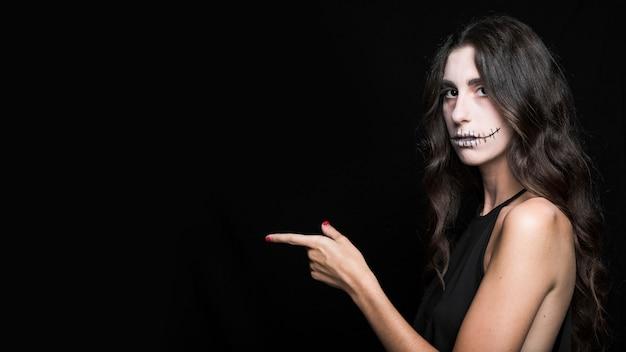 Mulher atraente com maquiagem espantalho apontando para a esquerda