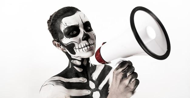 Mulher atraente com maquiagem esqueleto segurar o megafone
