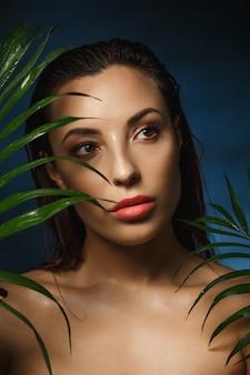 Mulher atraente com maquiagem fresca, cabelos molhados, olhando para longe.