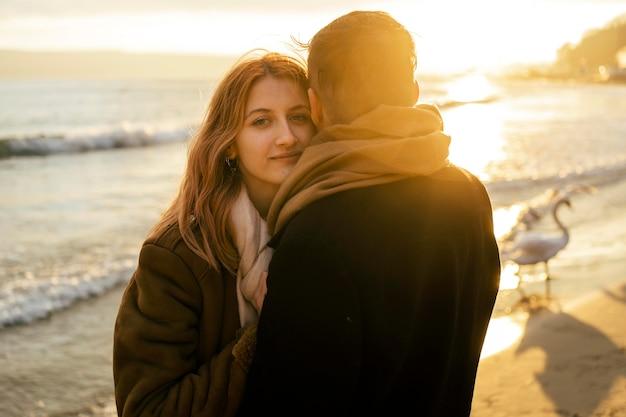 Mulher atraente com o namorado na praia no inverno