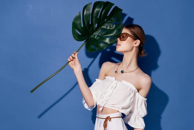 Mulher atraente com óculos brincos de fundo azul