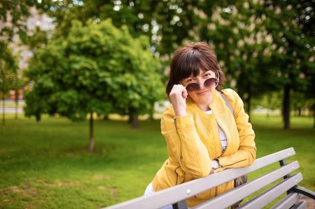 Mulher atraente com óculos de sol no parque