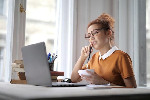 Mulher atraente com óculos, segurando uma tigela de cereal e sentada na frente de um laptop na mesa