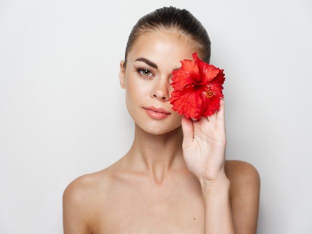 Mulher atraente com ombros nus segurando uma flor vermelha na frente do rosto