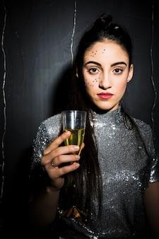 Mulher atraente com ornamento brilha no rosto e vidro por lado