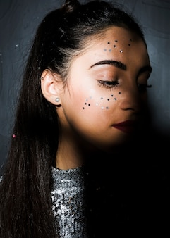Mulher atraente com ornamento brilha no rosto