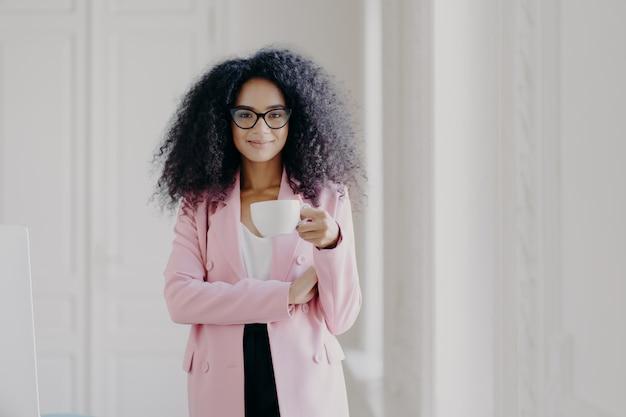 Mulher atraente com penteado afro, bebe bebida aromática, usa óculos