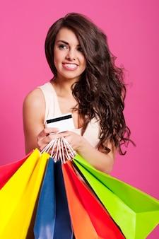 Mulher atraente com sacolas de compras e cartão de crédito