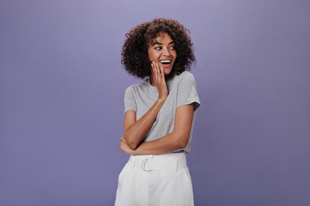 Mulher atraente com saia branca sorrindo e posando na parede isolada