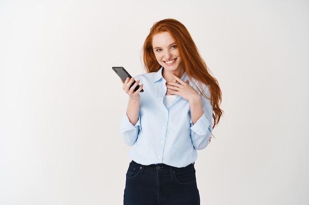 Mulher atraente com smartphone rindo e sorrindo na frente. rede social jovem com longos cabelos vermelhos, em pé sobre uma parede branca