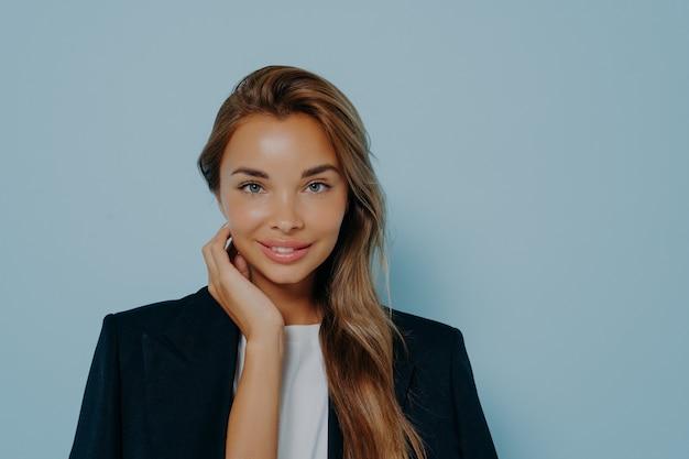Mulher atraente com sorriso gentil em fundo azul claro
