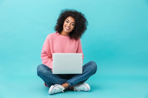 Mulher atraente com sorriso lindo usando notebook prata, enquanto está sentado em posição de lótus no chão, isolado sobre a parede azul