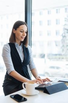 Mulher atraente com um sorriso fofo tomando um café enquanto relaxa em uma pausa com um tablet digital