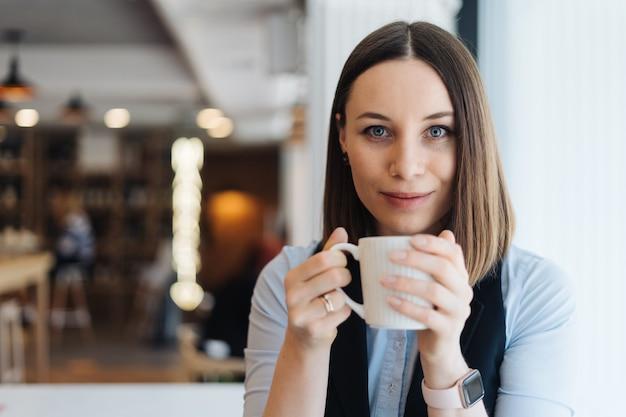 Mulher atraente com um sorriso fofo tomando um café enquanto relaxa em uma pausa