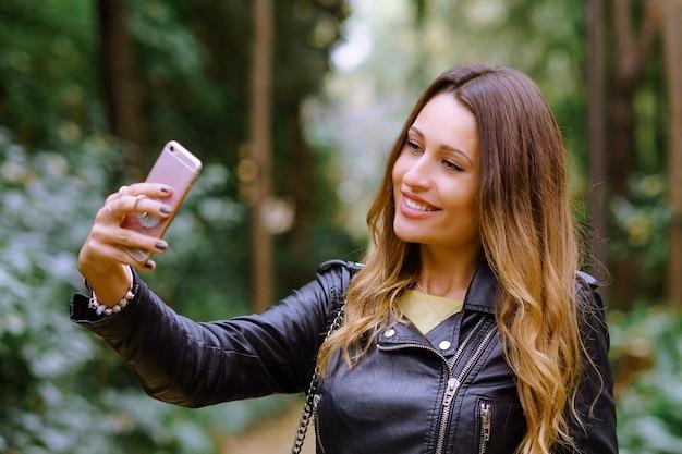 Mulher atraente, com um sorriso no rosto, tomando uma selfie no telefone