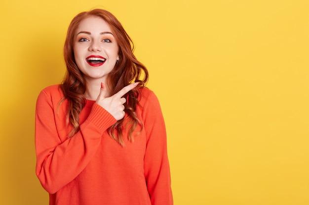 Mulher atraente com uma expressão feliz apontando para o espaço da cópia com o dedo indicador, vestida com um suéter laranja casual, modelos contra uma parede amarela, fêmea de gengibre com expressão animada.