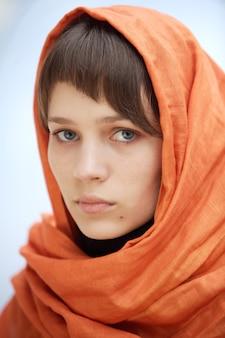 Mulher atraente com véu na cabeça um fundo azul (foco no olho)