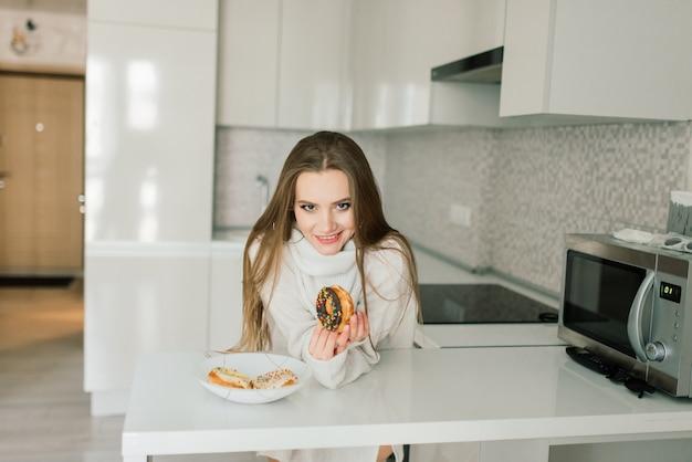 Mulher atraente com xícara de café, smartphone e bolos na cama