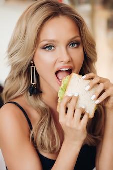 Mulher atraente, comendo sanduíche delicioso no café