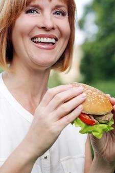 Mulher atraente, comer em um parque