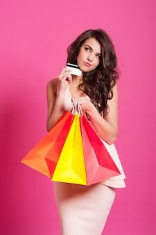 Mulher atraente confusa com cartão de crédito e sacolas de compras