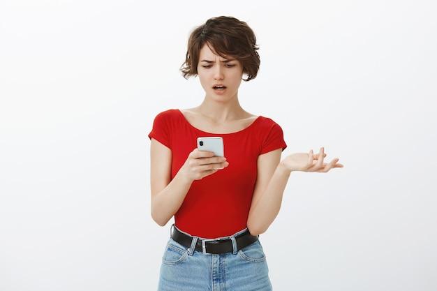 Mulher atraente confusa e intrigada, parecendo questionada, segurando o telefone, não consegue entender a mensagem