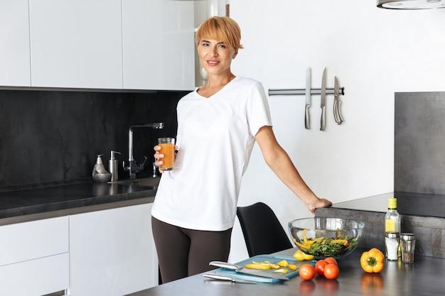 Mulher atraente cozinhando o almoço enquanto está na cozinha de casa, bebendo suco