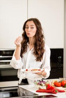 Mulher atraente cozinhar deliciosa refeição de peixe e legumes na cozinha